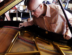 Pat Roak inspects the inside of a grand piano.